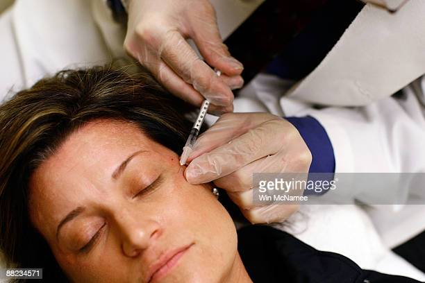 Recently laid off worker Lyn Talent receives a free Botox injection during an event called the 'The Botox Bailout' where the first 50 recently...