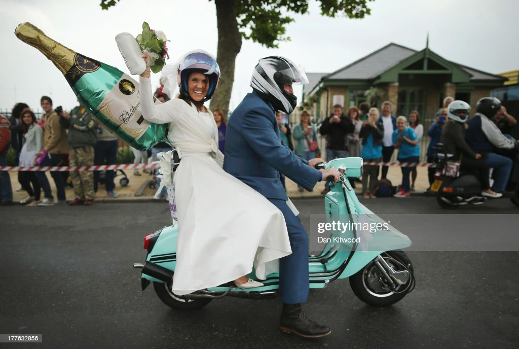 A recently married couple wave to the crowd as they participate in the 'Ride Out', which brings the scooter festival to a close on August 25, 2013 in Ryde, England. The annual event, which is organized by the British Scooter Rally Association and The VFM Scooter Collective, attracts around 6000 riders each year and has been running since 1980. The scooter in 1960s Britain was a fashion statement and the often heavily customized bikes, usually an Italian Vespa or Lambretta, became synonymous with the Mod scene. They provided an inexpensive mode of transport and escapism to an upwardly mobile youth at a time when public transportation stopped early. The Vespa was depicted on the cover of The Whos Quadrophenia album in 1973.
