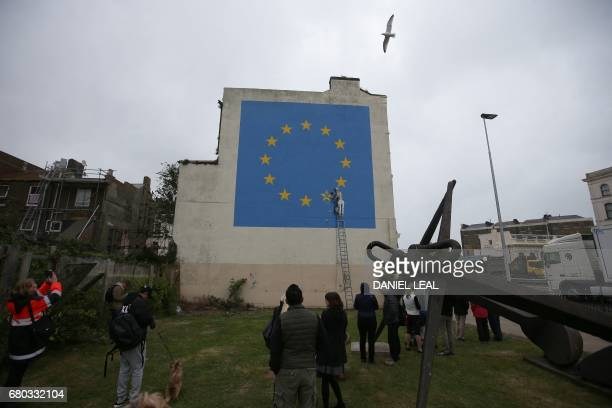 A recently painted mural by British graffiti artist Banksy depicting a workman chipping away at one of the stars on a European Union themed flag is...