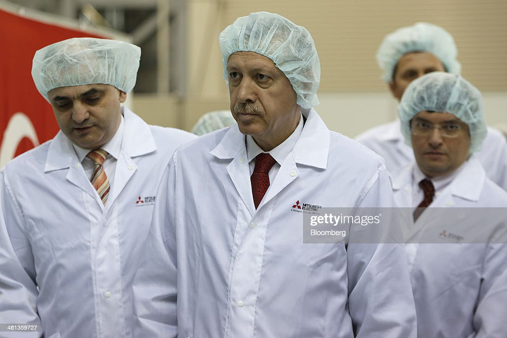 Recep Tayyip Erdogan, Turkey's prime minister, center, and Ozkan Dalbay, chief executive officer of Turksat AS, left, arrive for a ceremony marking the shipment of Turksat AS's Turksat-4A communications satellite, manufactured by Mitsubishi Electric Corp., at the company's satellite production facility at Kamakura Works in Kamakura, Kanagawa Prefecture, Japan, on Wednesday, Jan. 8, 2014. Turksat AS is Turkey's state-owned satellite operator. Photographer: Kiyoshi Ota/Bloomberg via Getty Images