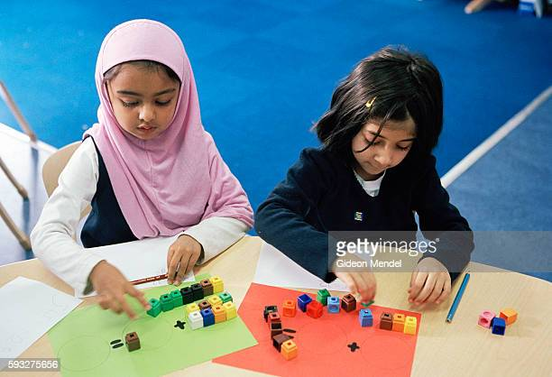 Reception children at Millfields Community school learn addition with colourful plastic beads during a Numeracy classThis is a large innercity...