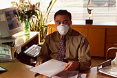 Receptionist at desk wearing an allergy mask