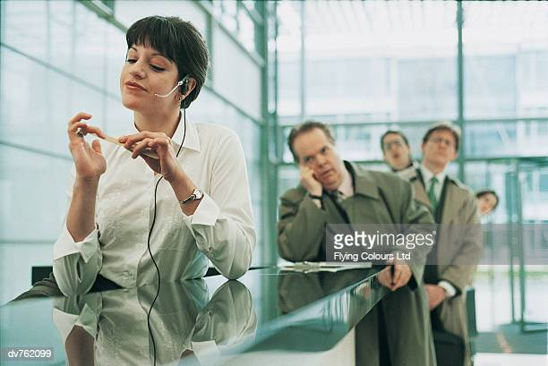 Receptionist Filing Her Nails as Business People Wait at Her Desk