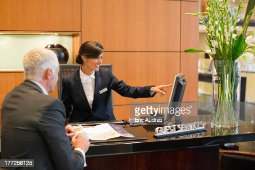 Receptionist Pointing On A Desktop Pc With A Businessman