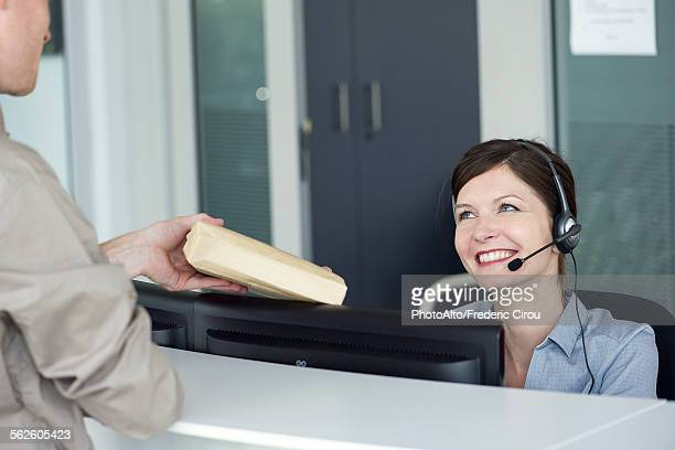 Receptionist receiving package from delivery person