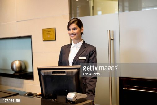 Receptionist Standing At The Hotel Reception Counter And