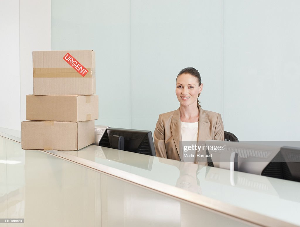 Receptionist with boxes at her desk : Stock Photo