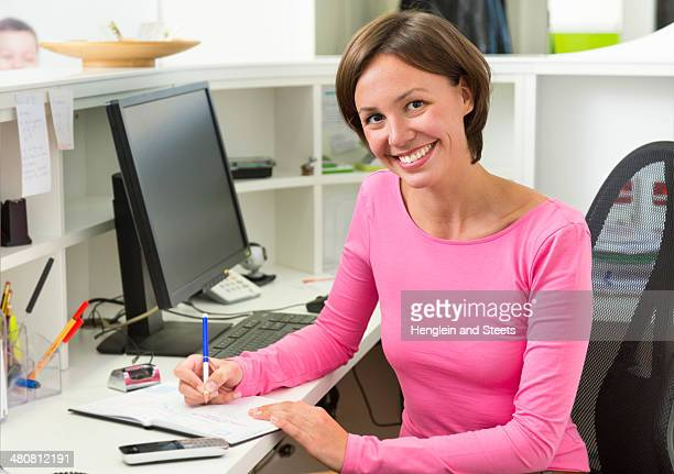 Receptionist writing at desk