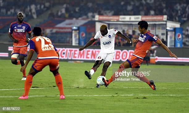 Rechard Gadze of Delhi Dynamos FC shuffles with FC Pune City during the India Super League football match on October 27 2016 in New Delhi India