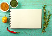 Recipe book and spices on blue wooden background