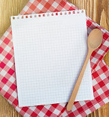 Recipe white page on picnic cloth on wooden background.Paper with copyspace for kitchen notes.Clean blank.