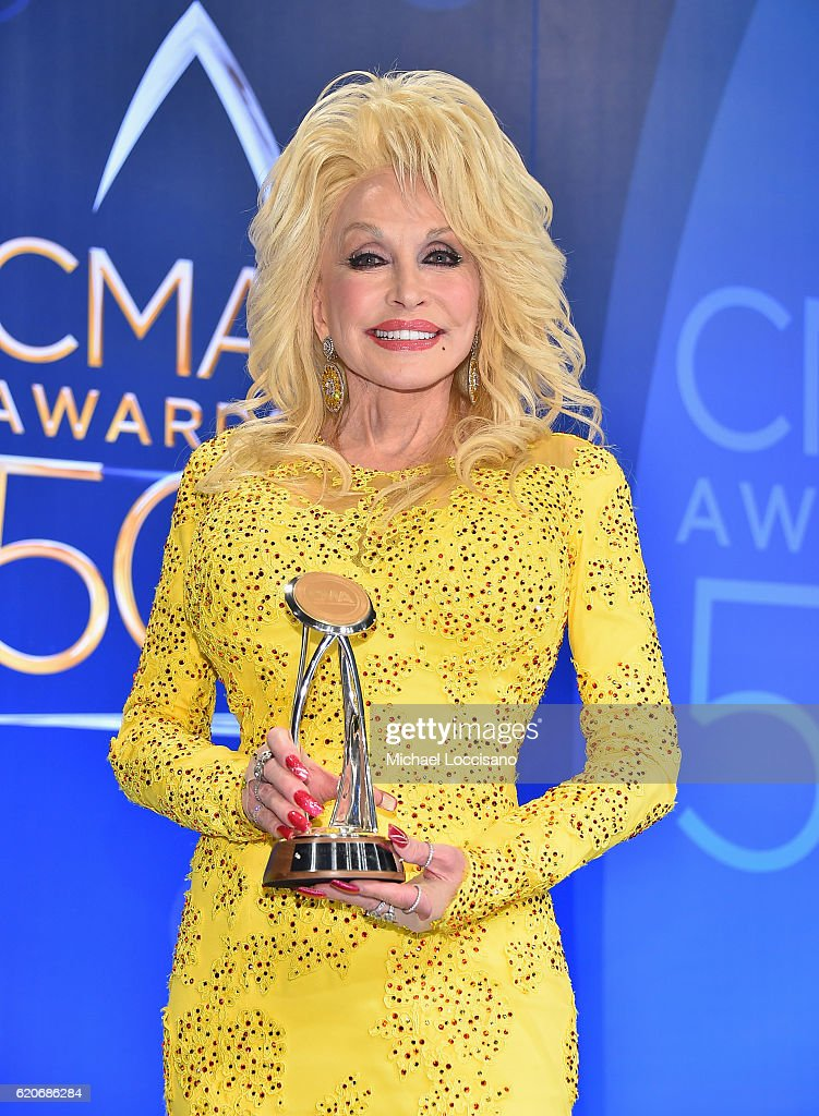 Recipient of the Willie Nelson Lifetime Achievement Award Dolly Parton poses backstage the 50th annual CMA Awards at the Bridgestone Arena on November 2, 2016 in Nashville, Tennessee.