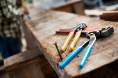 A reclaimed lumber workshop. A person at a workbench, and tools, grippers and pliers lined up on a plank of wood.