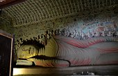 Ancient reclining Buddha statue at the Mogao Caves, an oasis located at a religious and cultural crossroads on the Silk Road, Dunhuang, Gansu province, China. The caves contain some of the finest exam