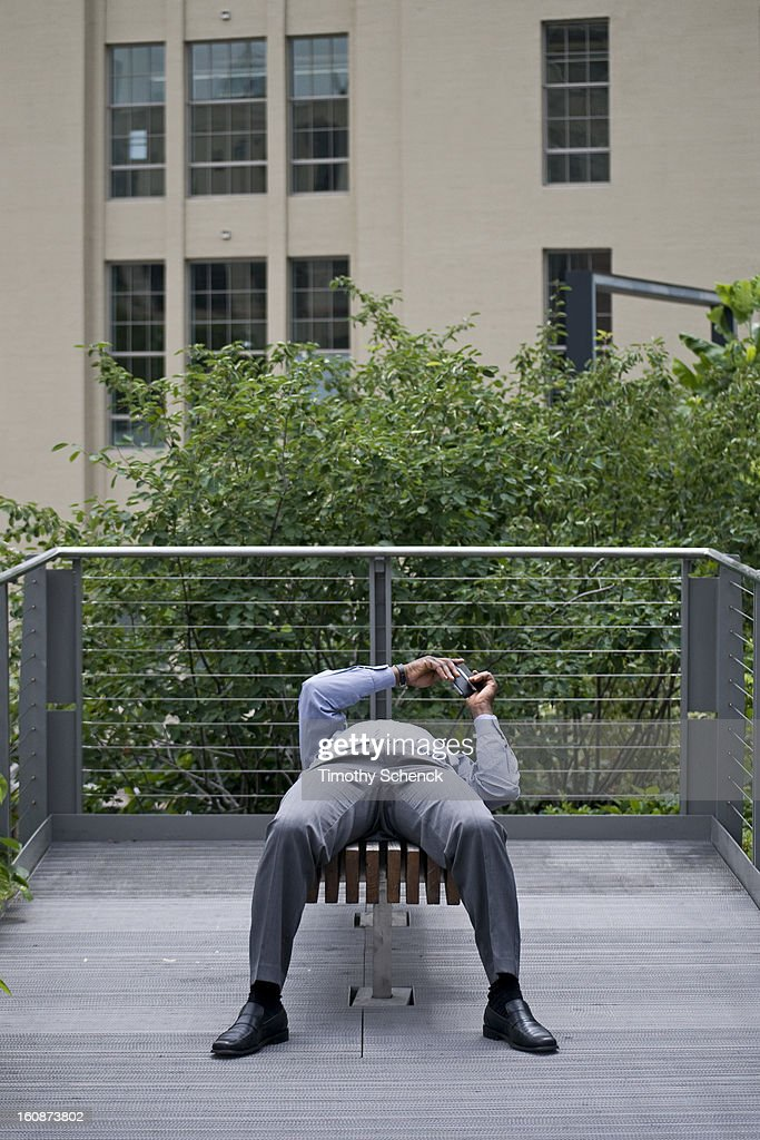 CONTENT] A reclining man relaxes and texts while enjoying the High Line park, Chelsea, NYC, June 2012.