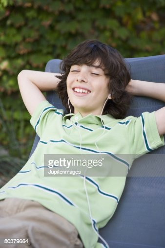 Reclining preteen boy with earbuds