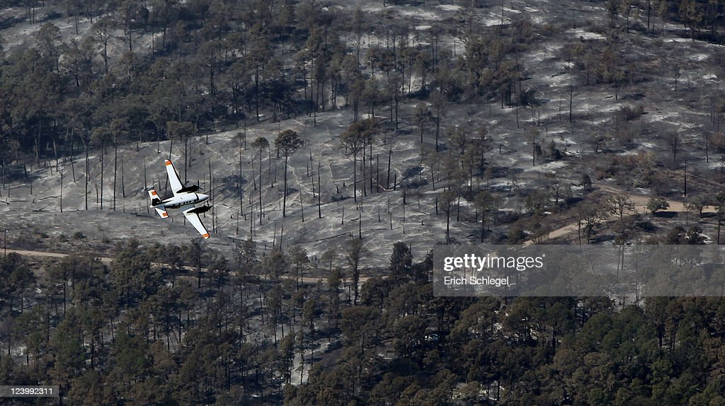 A reconnaissance plane flies over a burned area September 7, 2011 in Bastrop, Texas. Several large wildfires have been devastating Bastrop County for the last three days, but are now 30 percent contained, according to the Texas Forest Service.