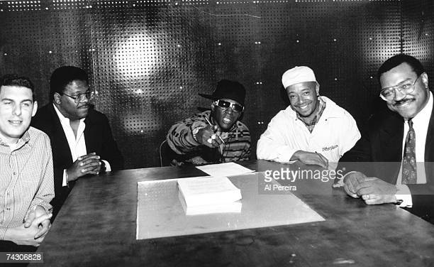 Record executive Lyor Cohen a lawyer rapper Flavor Flav record executive Russell Simmons and a lawyer pose for a portrait as Flav signs a solo deal...