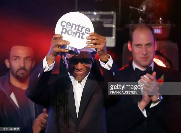 US record producer Nile Rodgers raises a Centerpoint award presented by Britain's Prince William Duke of Cambridge during Centrepoint at the Palace a...
