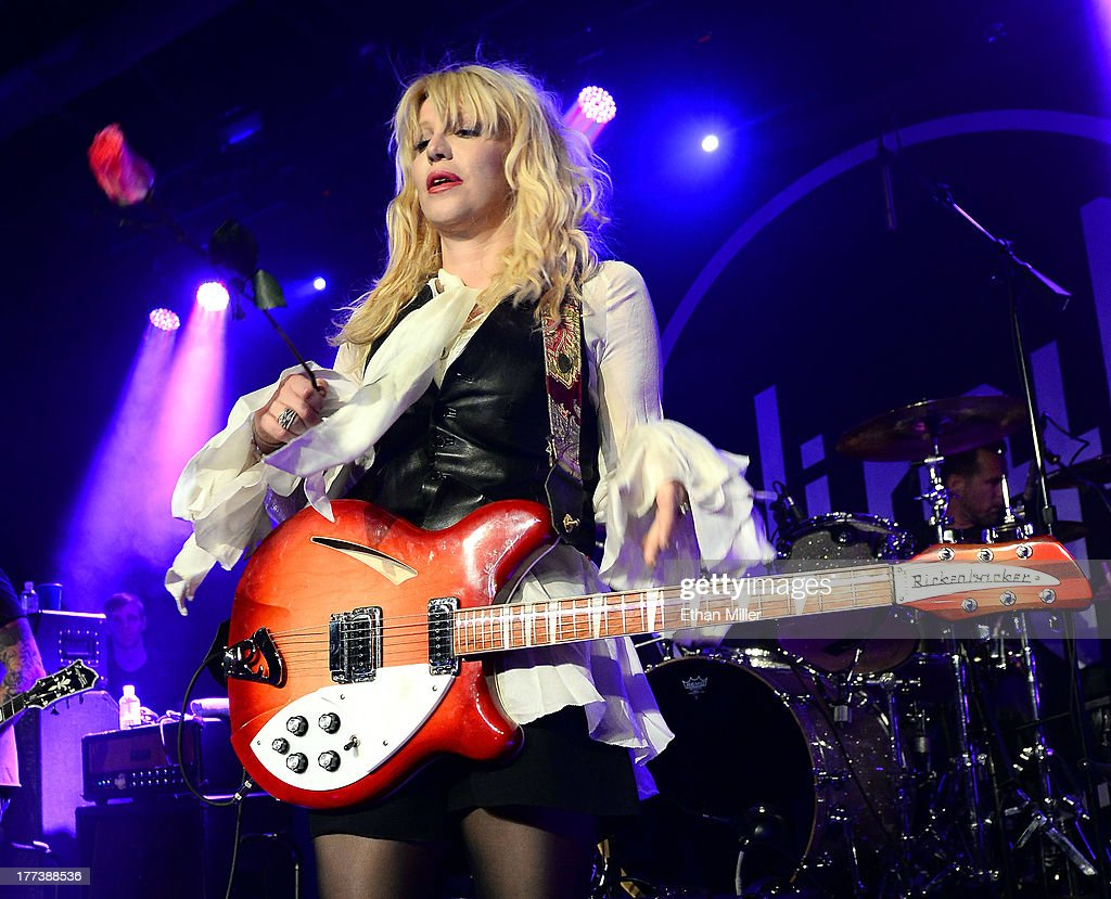 Recording artist <a gi-track='captionPersonalityLinkClicked' href=/galleries/search?phrase=Courtney+Love&family=editorial&specificpeople=156418 ng-click='$event.stopPropagation()'>Courtney Love</a> prepares to throw a flower into the crowd as she performs at Vinyl inside the Hard Rock Hotel & Casino during the venue's anniversary celebration on August 22, 2013 in Las Vegas, Nevada.