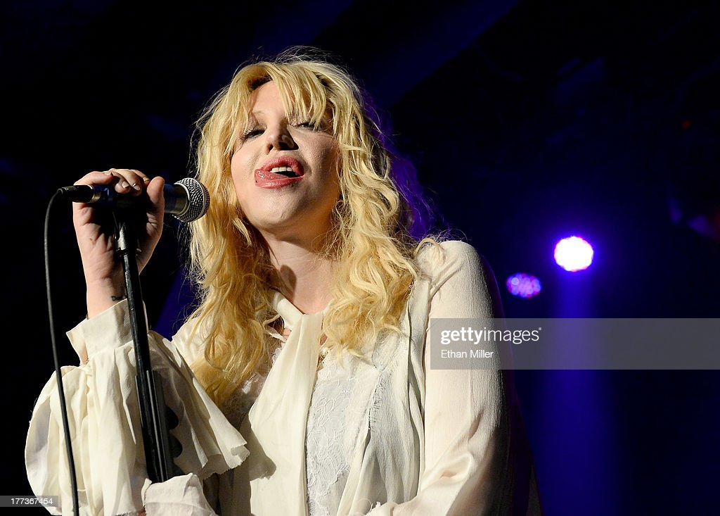 Recording artist Courtney Love sticks her tongue out as she performs at Vinyl inside the Hard Rock Hotel & Casino during the venue's anniversary celebration on August 22, 2013 in Las Vegas, Nevada.