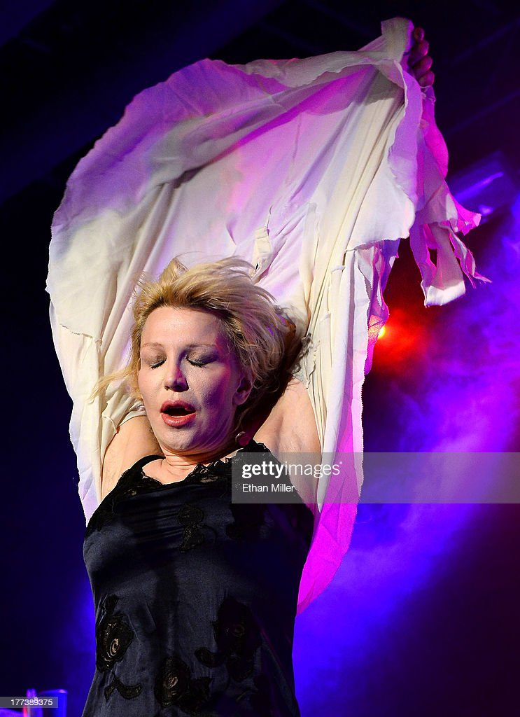 Recording artist Courtney Love takes off her blouse as she performs at Vinyl inside the Hard Rock Hotel & Casino during the venue's anniversary celebration on August 22, 2013 in Las Vegas, Nevada.