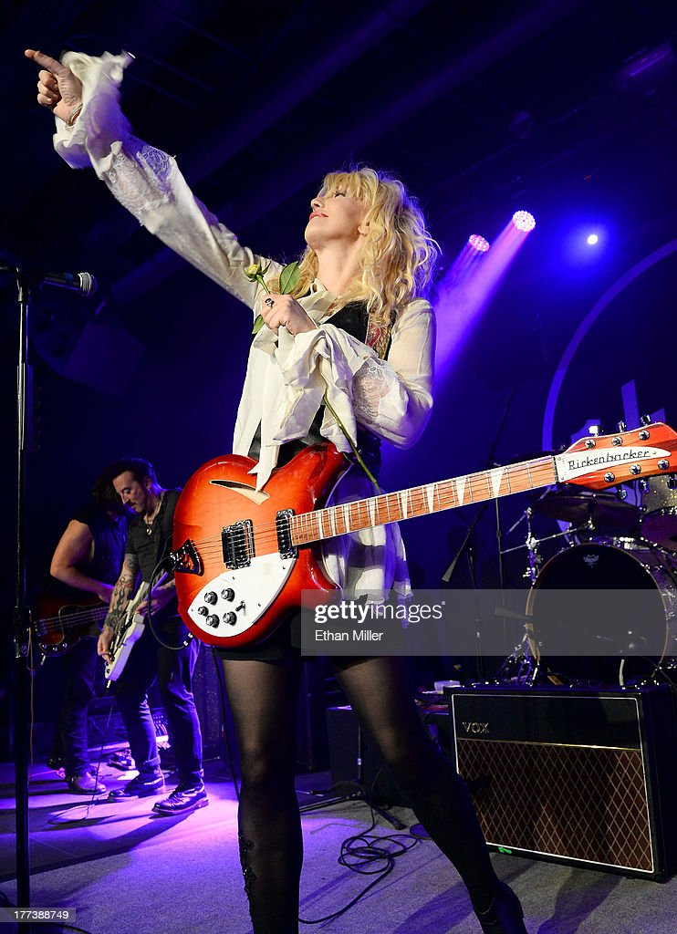 Recording artist Courtney Love throws a flower into the crowd as she performs at Vinyl inside the Hard Rock Hotel & Casino during the venue's anniversary celebration on August 22, 2013 in Las Vegas, Nevada.