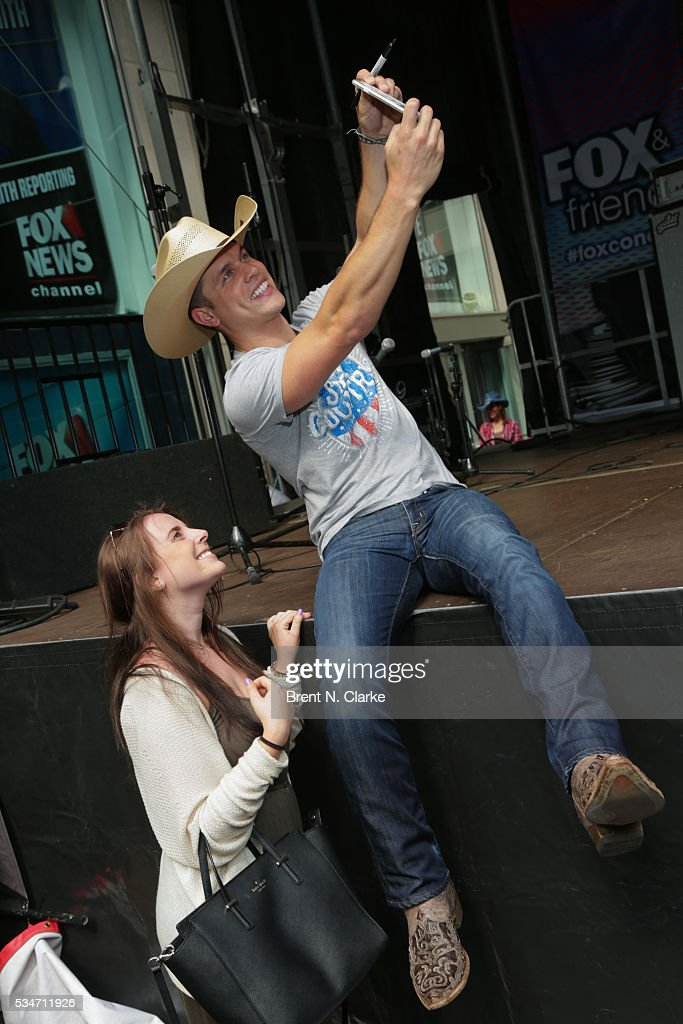 Recording artist <a gi-track='captionPersonalityLinkClicked' href=/galleries/search?phrase=Dustin+Lynch&family=editorial&specificpeople=8612719 ng-click='$event.stopPropagation()'>Dustin Lynch</a> poses for photographs with fans following his performance on the 'FOX & Friends' All American Concert Series outside of FOX Studios on May 27, 2016 in New York City.