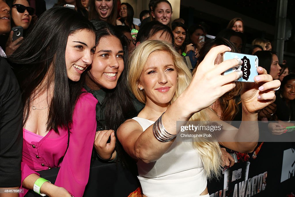 Recording artist <a gi-track='captionPersonalityLinkClicked' href=/galleries/search?phrase=Ellie+Goulding&family=editorial&specificpeople=6389309 ng-click='$event.stopPropagation()'>Ellie Goulding</a> (R) poses for a selfie with fans at the 2014 MTV Movie Awards at Nokia Theatre L.A. Live on April 13, 2014 in Los Angeles, California.