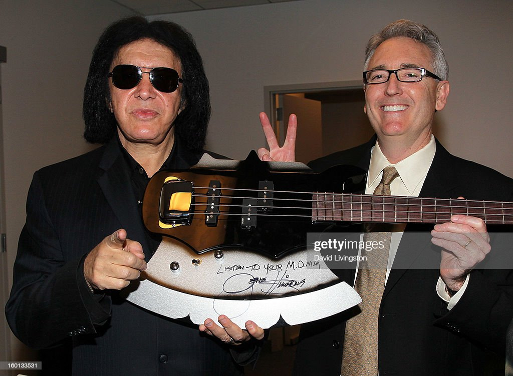 Recording artist <a gi-track='captionPersonalityLinkClicked' href=/galleries/search?phrase=Gene+Simmons&family=editorial&specificpeople=138593 ng-click='$event.stopPropagation()'>Gene Simmons</a> (L) and NAMM president and CEO Joe Lamond pose with a guitar donated to the Museum of Making Music by Simmons at the 2013 NAMM Show - Day 3 at the Anaheim Convention Center on January 26, 2013 in Anaheim, California.