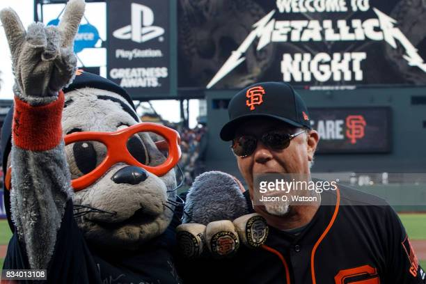 Recording artist James Hetfield of the rock band Metallica stands on the field with San Francisco Giants mascot Lou Seal before the game against the...