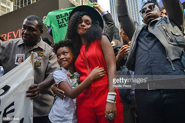 Recording artist Janelle Monae stands with her arm around a young girl at the conclusion of the march Members of the Stop Mass Incarceration Network...