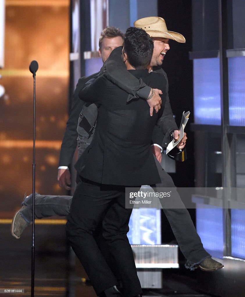 Recording artist Jason Aldean jumps into the arms of co-host Luke Bryan after Aldean accepted the Entertainer of the Year award during the 51st Academy of Country Music Awards at MGM Grand Garden Arena on April 3, 2016 in Las Vegas, Nevada.