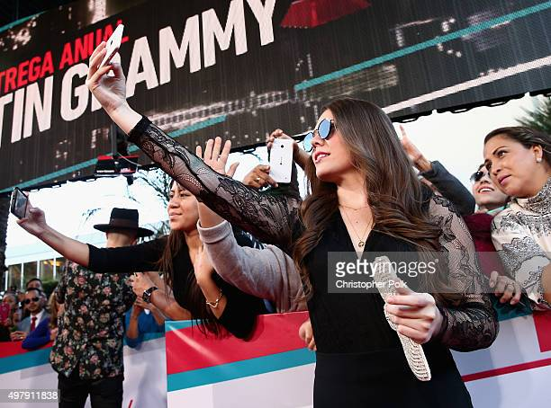Recording artist Joy Huerta of music group Jesse y Joy poses for a selfie photo with fans at the 16th Latin GRAMMY Awards at the MGM Grand Garden...
