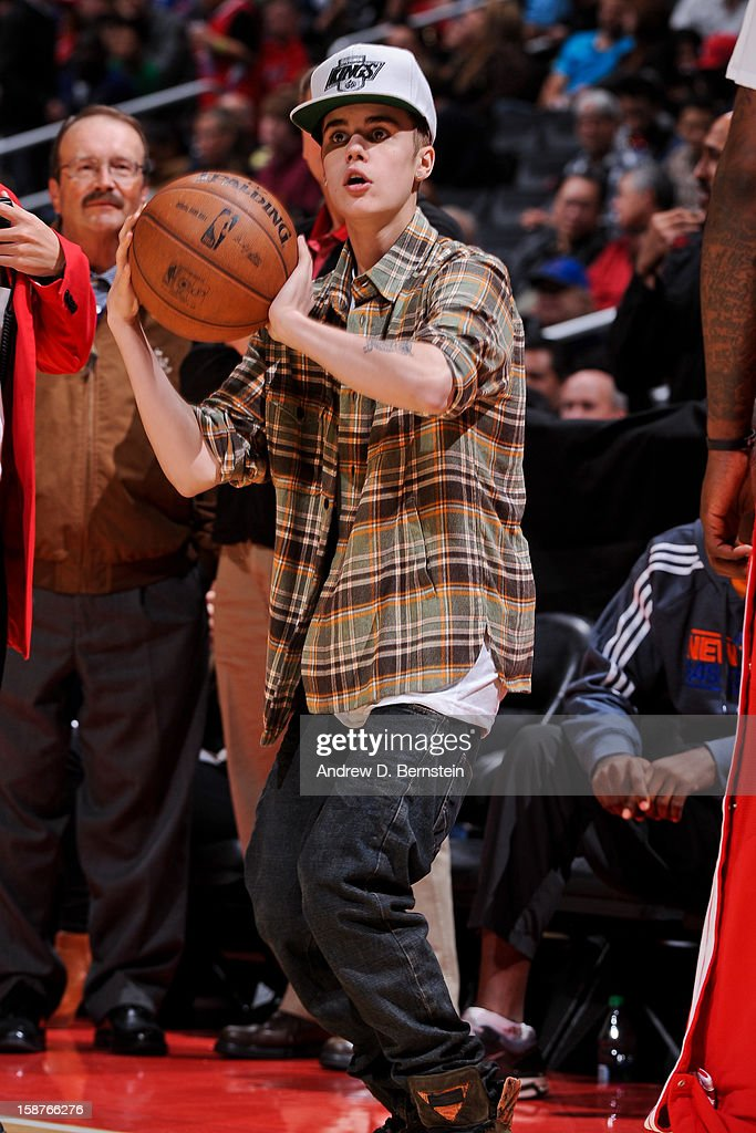 Recording artist Justin Bieber shoots a basketball during a break in a game between the Boston Celtics and Los Angeles Clippers on December 27, 2012 at the Staples Center in Los Angeles, California.