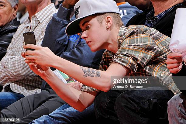 Recording artist Justin Bieber takes a picture using an Apple Inc iPhone 5 during a game between the Boston Celtics and Los Angeles Clippers on...