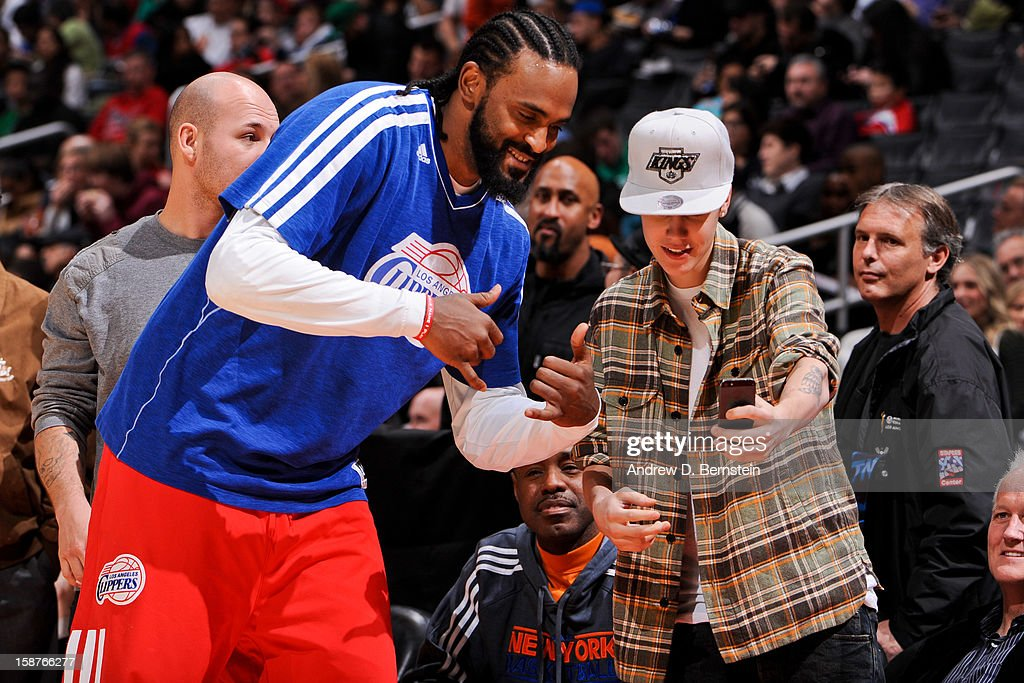 Recording artist Justin Bieber takes a picture with Ronny Turiaf #21 of the Los Angeles Clippers during a game between the Boston Celtics and Clippers on December 27, 2012 at the Staples Center in Los Angeles, California.