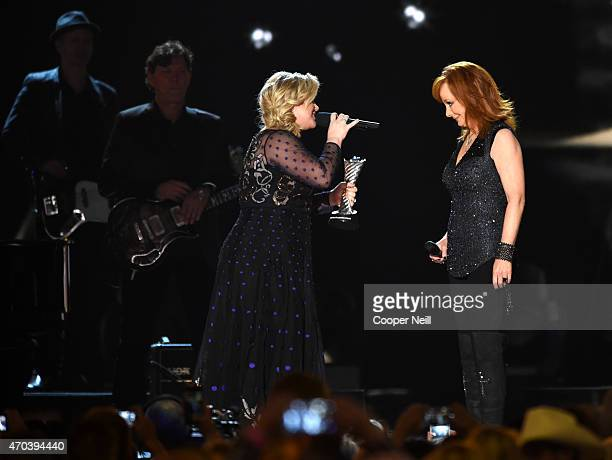 Recording artist Kelly Clarkson presents the 50th Anniversary Milestone Award to honoree Reba McEntire onstage during the 50th Academy Of Country...