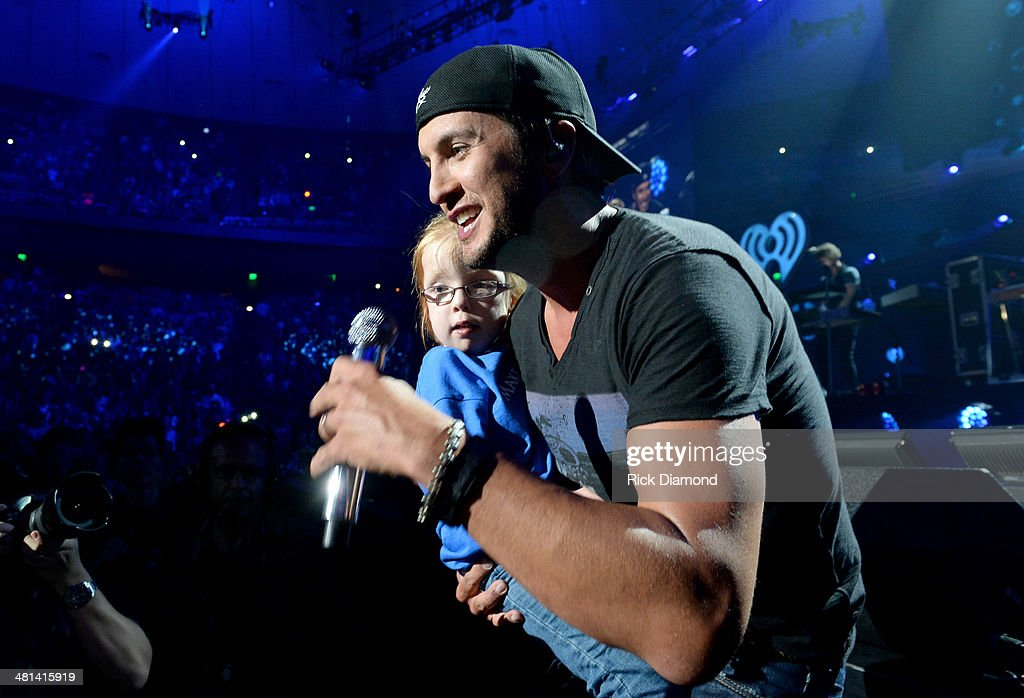 Recording artist Luke Bryan (R) interacts with six-year-old Sadie Moore of Kentucky onstage during iHeartRadio Country Festival in Austin at the Frank Erwin Center on March 29, 2014 in Austin, Texas.