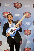 Recording artist Randy Houser poses with the award for Most Played Radio Track in the press room during the American Country Awards 2013 at the...