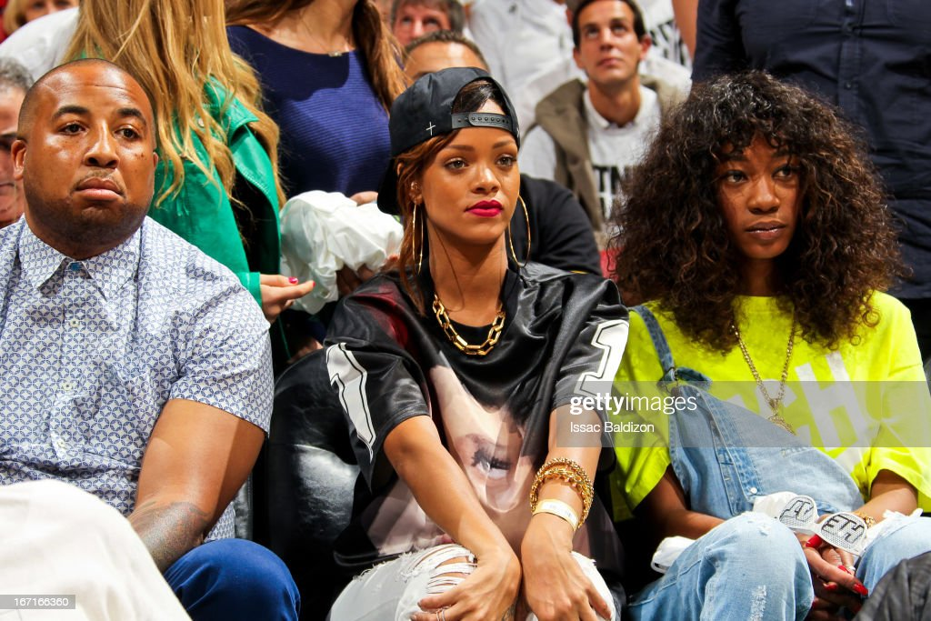 Recording artist Rihanna (C) and Melissa Forde (R) sit court-side as the Milwaukee Bucks play the Miami Heat in Game One of the Eastern Conference Quarterfinals during the 2013 NBA Playoffs on April 21, 2013 at American Airlines Arena in Miami, Florida.