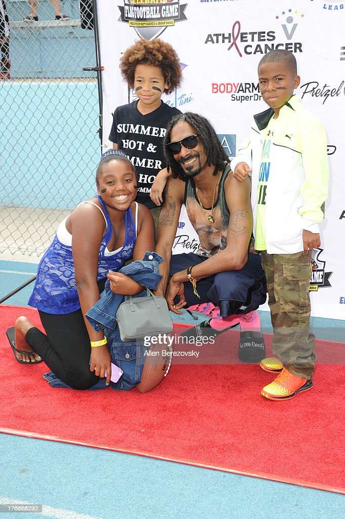 Recording artist Snoop Dogg poses for a picture with kids at the 1st Annual Athletes VS Cancer Celebrity Flag Football Game on August 18, 2013 in Pacific Palisades, California.
