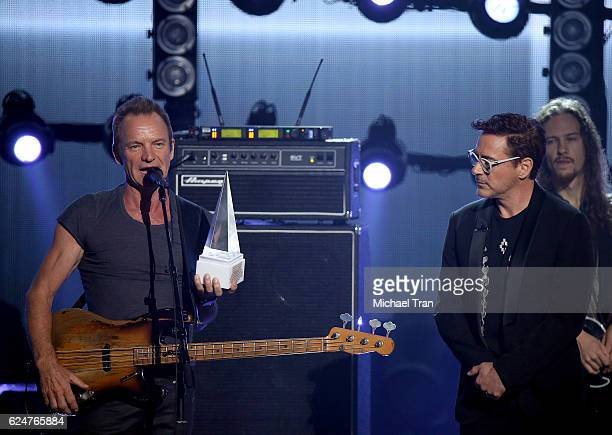 Recording artist Sting accepts the Award of Merit from actor Robert Downey Jr onstage during the 2016 American Music Awards held at Microsoft Theater...