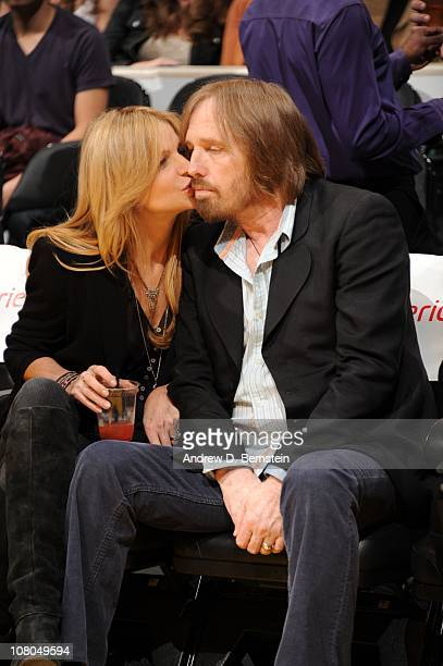 Recording artist Tom Petty is kissed by his wife Dana York during a game between the New Jersey Nets and the Los Angeles Lakers at Staples Center on...