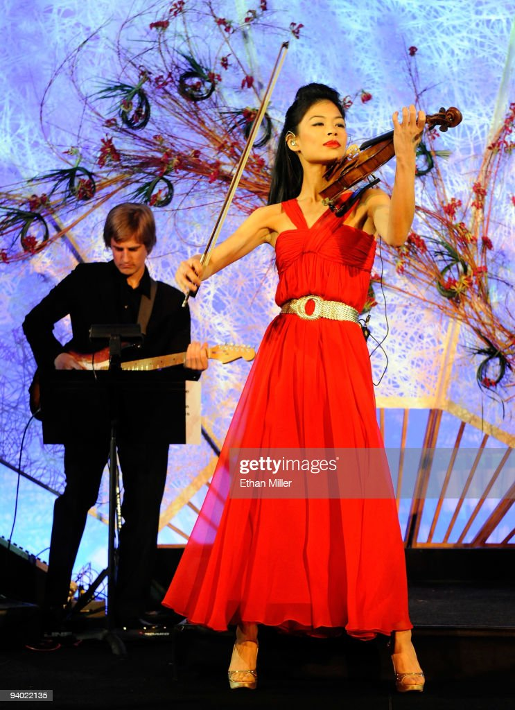 Recording artist Vanessa-Mae (R) performs during the opening night gala for Mandarin Oriental, Las Vegas at CityCenter December 4, 2009 in Las Vegas, Nevada. The 47-story nongaming luxury hotel and condominium tower is the third part of the 67-acre, USD 8.5 billion mixed-use urban development center to open. The joint project between MGM Mirage and Dubai World is said to be the biggest privately financed construction project in United States history and one of the world's largest green projects being built with the Leadership in Energy & Environmental Design (LEED) Gold certified Green Building Rating System.