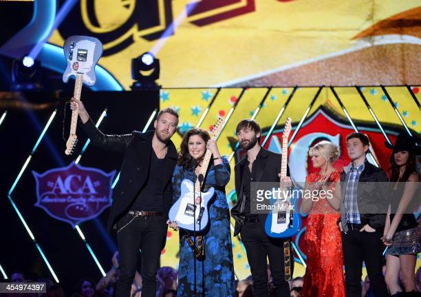 Recording artists Charles Kelley Hillary Scott and Dave Haywood of Lady Antebellum accept the award for Group of the Year from presenters Lauren...