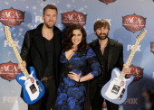 Recording artists Charles Kelley Hillary Scott and Dave Haywood of Lady Antebellum pose with the award for Group of the Year in the press room during...