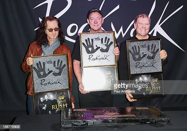 Recording artists Geddy Lee Neil Peart and Alex Lifeson of Rock Band Rush is honored on Guitar Center's RockWalk at Guitar Center on November 20 2012...
