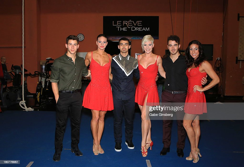 Recording artists Nick Jonas (L), Joe Jonas (3L) and Kevin Jonas (2R) pose for photos with cast members of Le Reve at Wynn Las Vegas on September 14, 2013 in Las Vegas, Nevada.