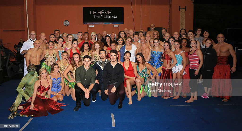 Recording artists Nick Jonas, Joe Jonas and Kevin Jonas pose for photos with cast members of Le Reve at Wynn Las Vegas on September 14, 2013 in Las Vegas, Nevada.